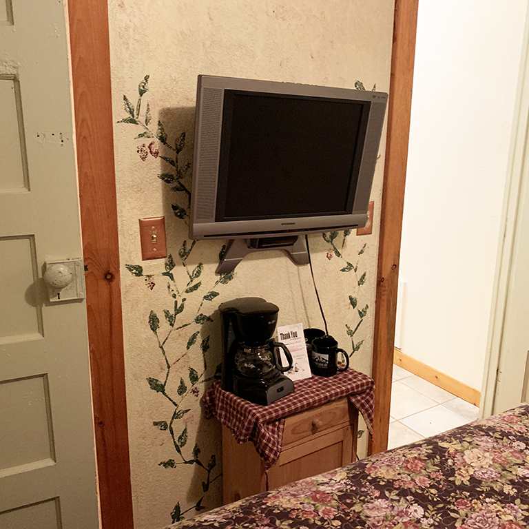 Flat screen TV mounted on the wall at the foot of the bed for movies